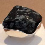 Srebrny pierścionek z czarnym kamieniem.