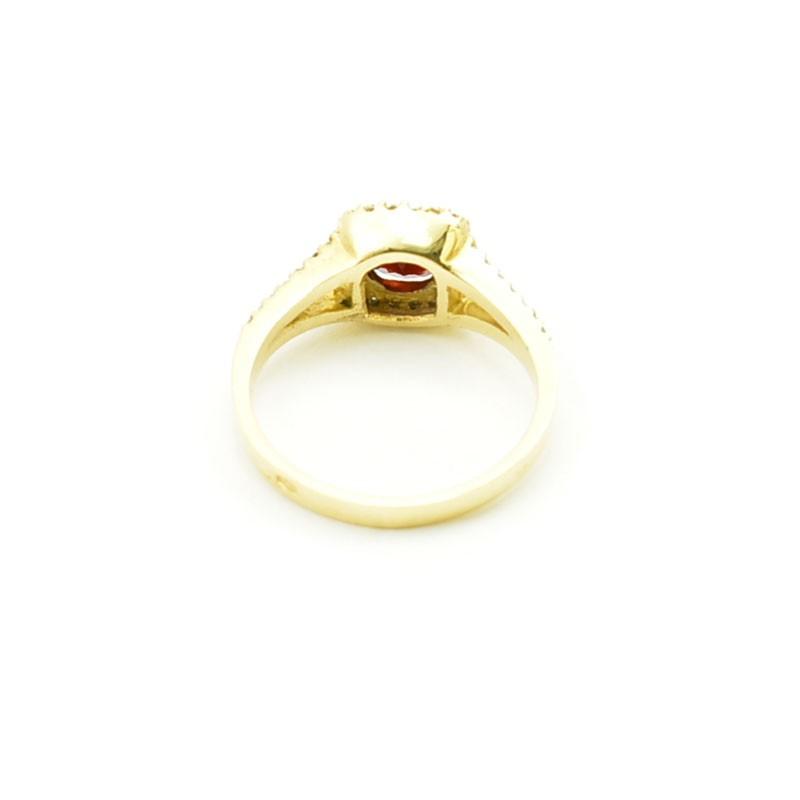 Wnętrze złotego pierścionka z granatem i cyrkoniami.