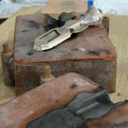 Odlana srebrna zawieszka z runami na formie z piasku.