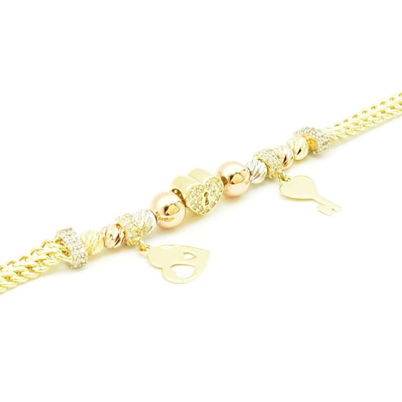 Przekładki, zawieszki i cyrkonie zdobiące złotą bransoletkę.